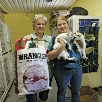 Doris Winstead with two rescued cats on the right and Judy Ingle with a shopping bag