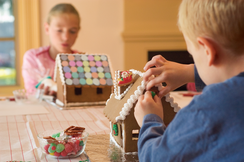 two children decorating gingerbread houses