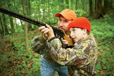 father helping his son aim a gun