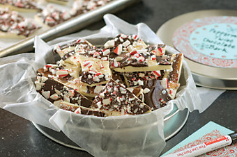 Peppermint Twist Chocolate Bark in a tin with wax paper lining