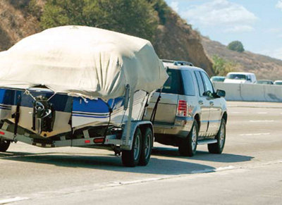 rearview of a truck pulling a trailer down the highway
