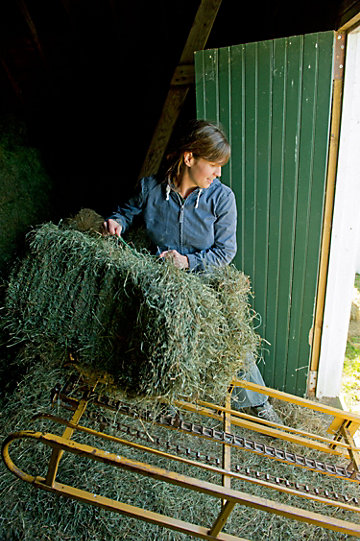 woman lifting a bale of hay