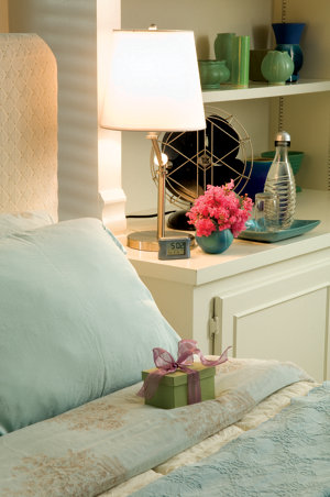 a bed prepared with a gift and several amenities included on the nightstand