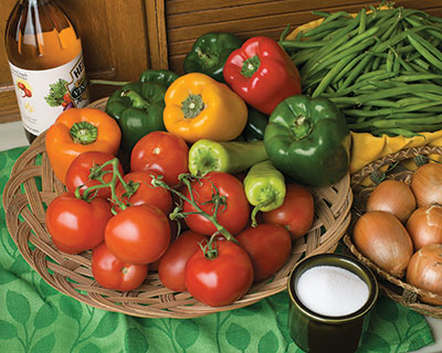 tomatoes and peppers in a basket, onions in a basket, a jar of vinegar, a small container of sugar