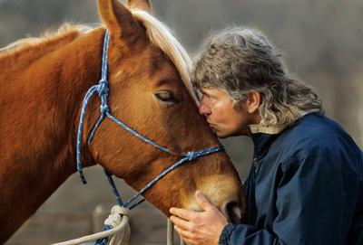 Jim Gilligan gently kissing a horse