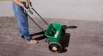 Man seeding a new lawn with seed spreader.