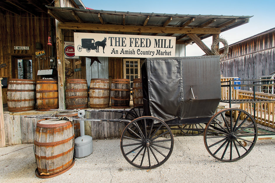 the outside front of the store with an old, unused Amish carriage in front as well as a bunch of old barrels