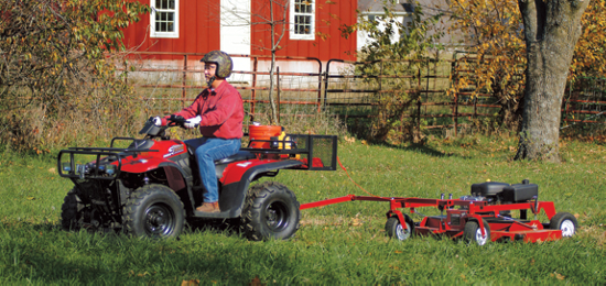 man riding an ATV pulling a yardwork accessory