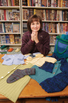 Patricia sitting behind some of her knitting works in progress