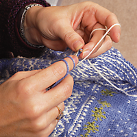 a person's hand in the act of knitting