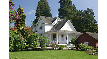 White house in the country with healthy lawn and garden.