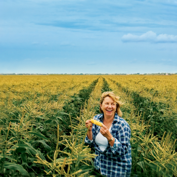 Teena standing in a field of corn with an ear of corn and laughing