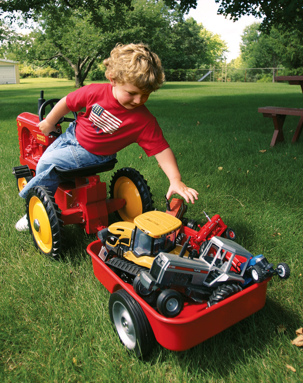 3-year-old Josef VonHandorf playing with tractors from Scale Models