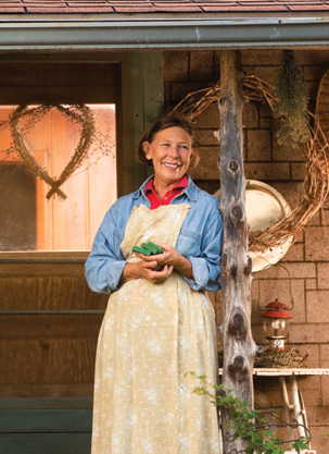 Gayl Bousman standing on her porch with a handful of her homemade soaps