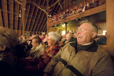 audience members laughing at a play