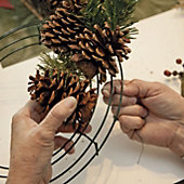 use the wire to attach the pine cones to the frame