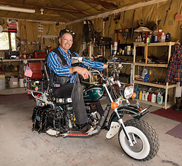 Richard Schwab sitting on his minibike in the garage