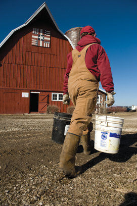 person in a hooded shirt carrying a bucket walking in front of a red barn