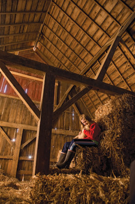 Mallary in the barn sitting up on some hay bales holding a cat