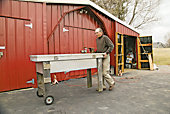 man wheeling a repurposed truck toolbox across a yard