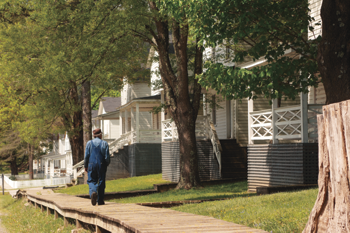 Artie walking away from the camera in his childhood neighborhood