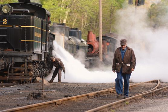 Artie walking along a railroad track in the railyard