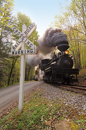 the train crossing a road with a railroad crossing sign in the foreground