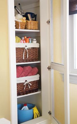 baskets and bins on the shelves inside a bathroom closet