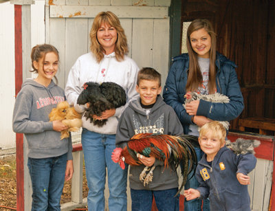 Shari with all of her children holding chickens