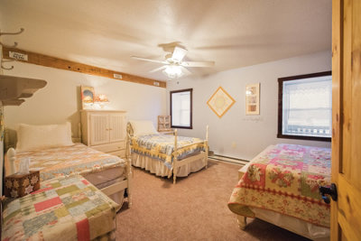 one of the bedrooms with quilts on every bed