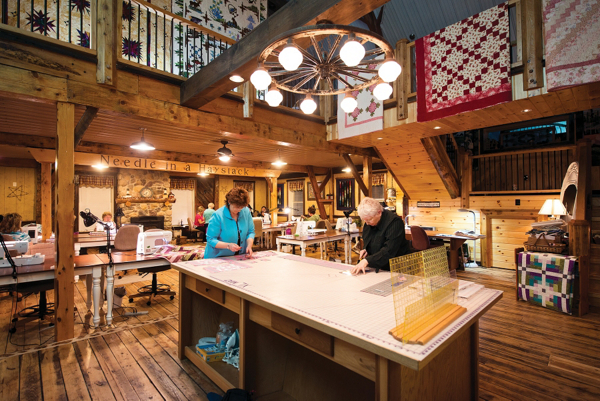 a picture of the main area: trimming table in the foreground, multiple tables and sewing machines in the background, quilts on display everywhere