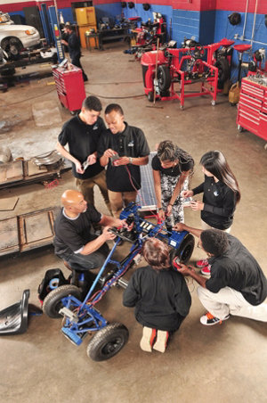 Greg working on a go-cart with a group of his students