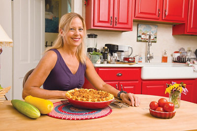 Beth sitting at her kitchen table with a pie in front of her