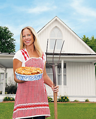 Beth Howard in front of American Gothic House with a pie and a pitchfork