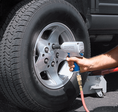 Using an air-powered tool to remove lug nuts from a car wheel