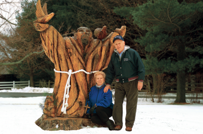 Julie and Bill Zink in front of the wooden statue of St. Francis - Tractor Supply Co.