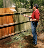 man pressure-washing a wooden fence