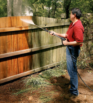 Man using a pressure washer on a wooden fence.