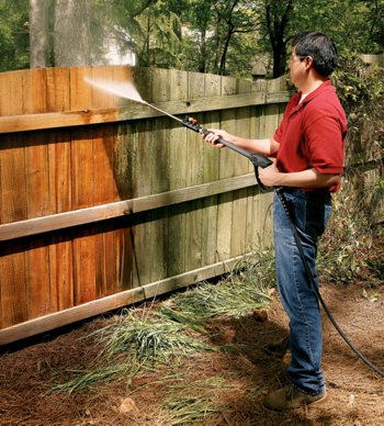 man using a pressure washer on a wooden fence