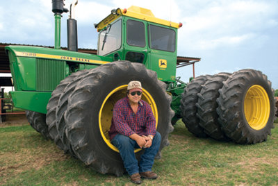 Francis sitting in the front wheel well of his John Deere 7020
