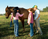 Rebecca demonstrating horse-care to two beginning riders