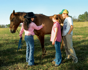 Rebecca showing horse-care to two beginning riders