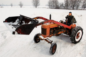 Spencer using one of his restored tractors with a shovel attachment for the snow