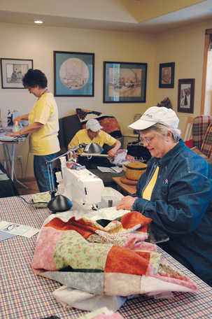 people in a craft room working on various crafts