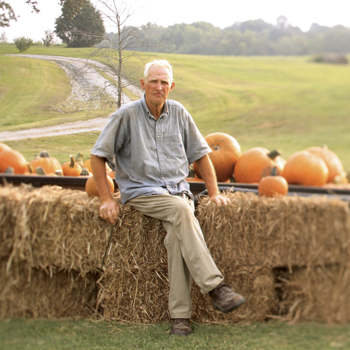 Jimmy sitting on a hay bale next to some freshly harvested pumpkins