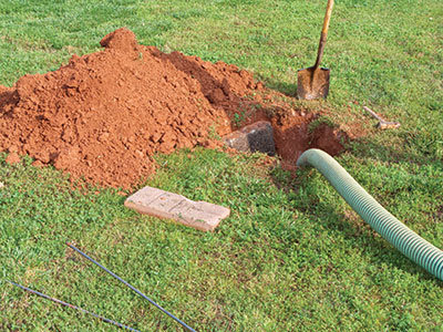 A septic tank access in a yard with the dirt piled to the side and a pipe coming out of the tank - Tractor Supply Co.