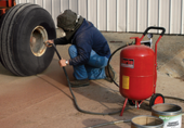man in a hood kneeling with a portable sandblaster