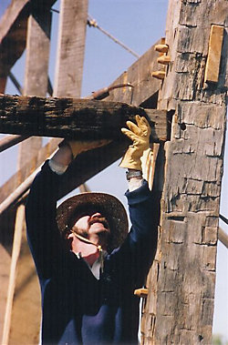 a man working on dismantling a barn