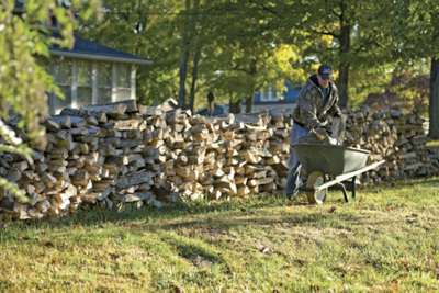 man taking cut firewood out of a wheelbarrow to stack