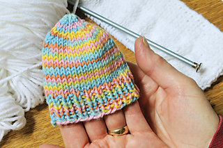 a finished knit cap for a premature baby fits around just four fingers